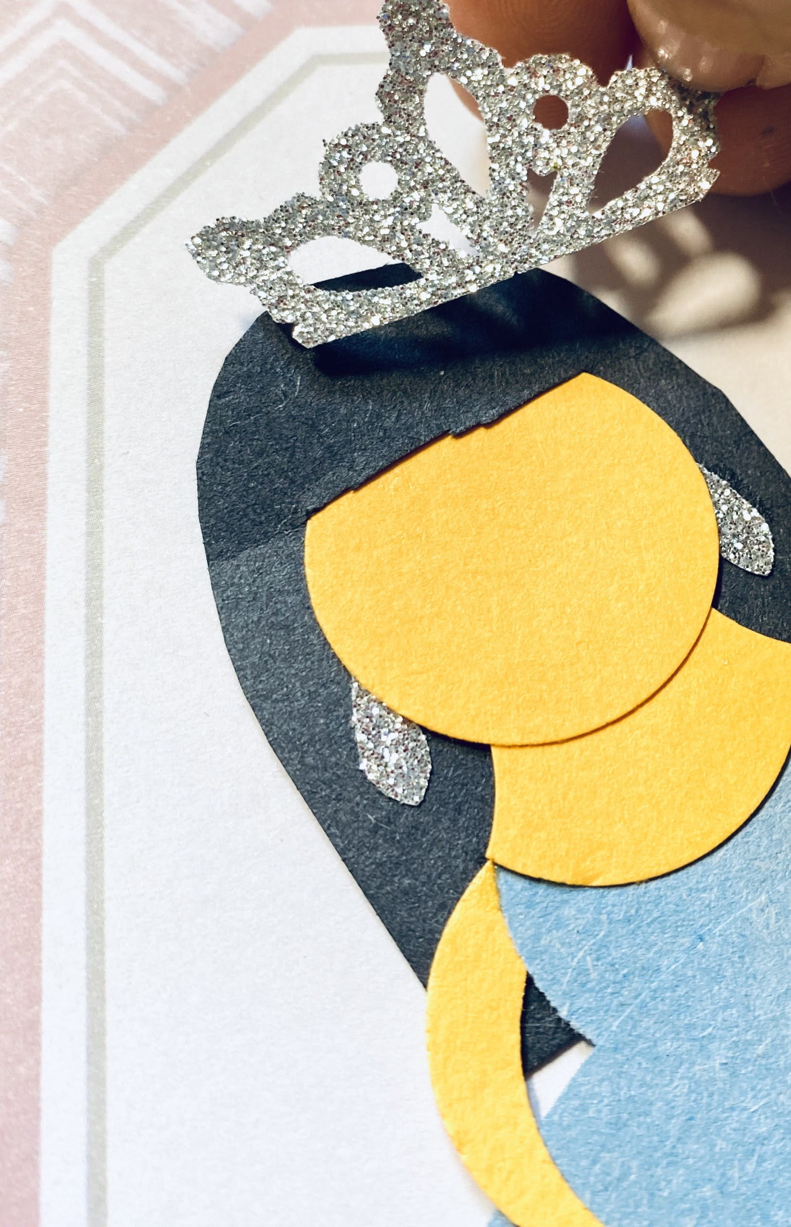 Here we are adding a glittery silver crown to the paper princess.  She also has her glittery earrings on.