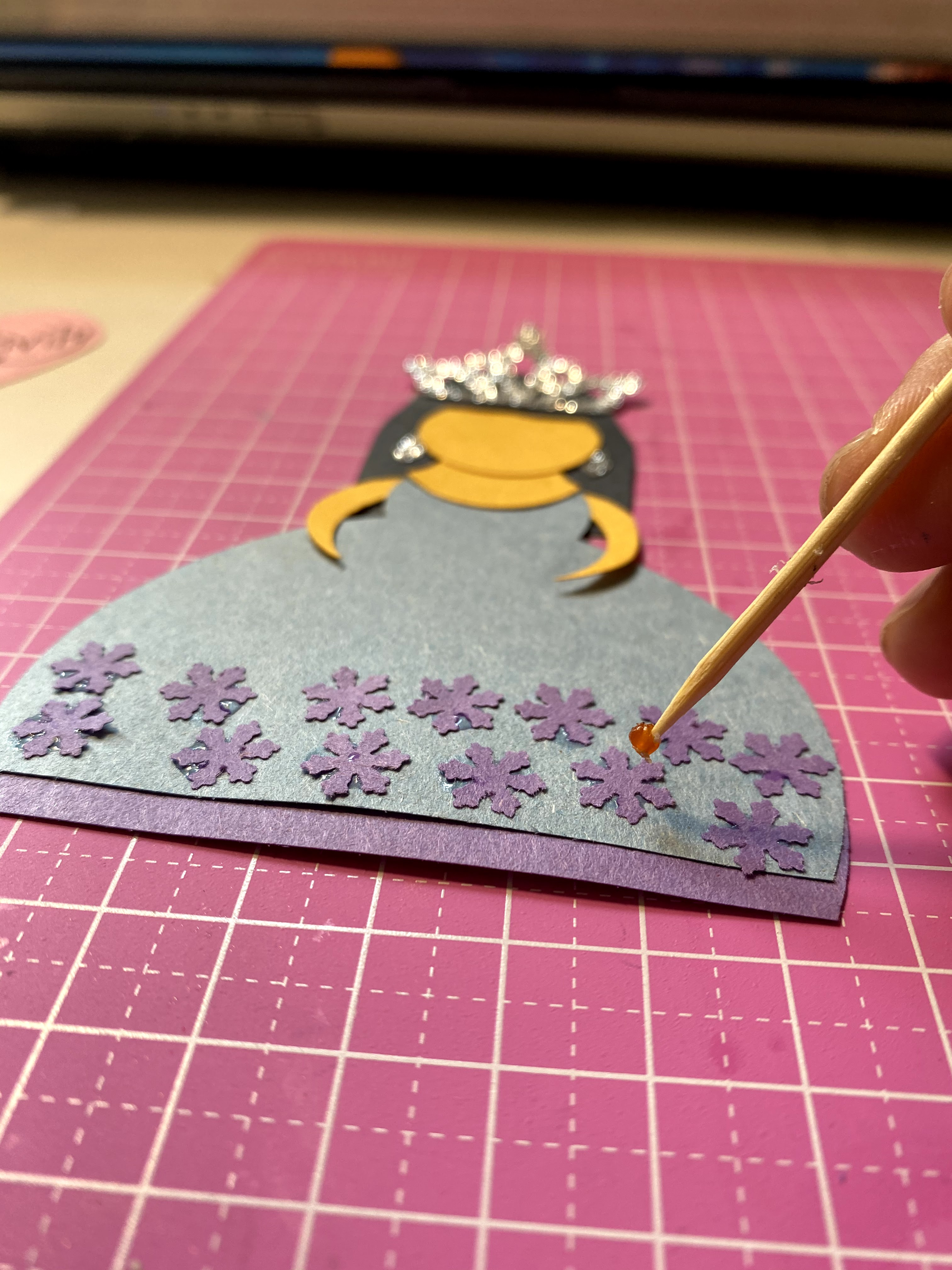 Adding small snowflake paper punches to decorate the paper princess dress.