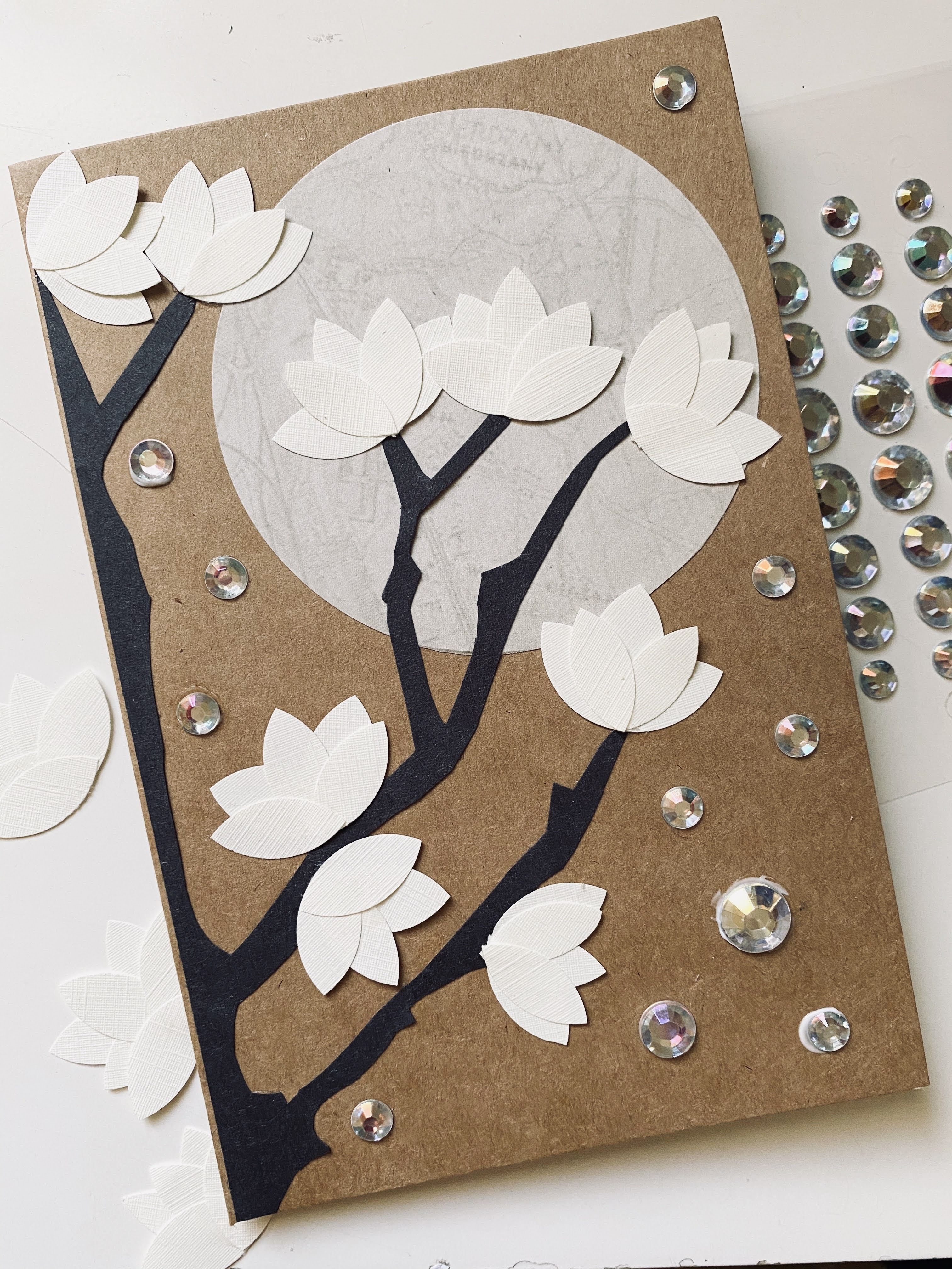 Textured cream colored Magnolias on black branches with a full moon and rhinestone stars.