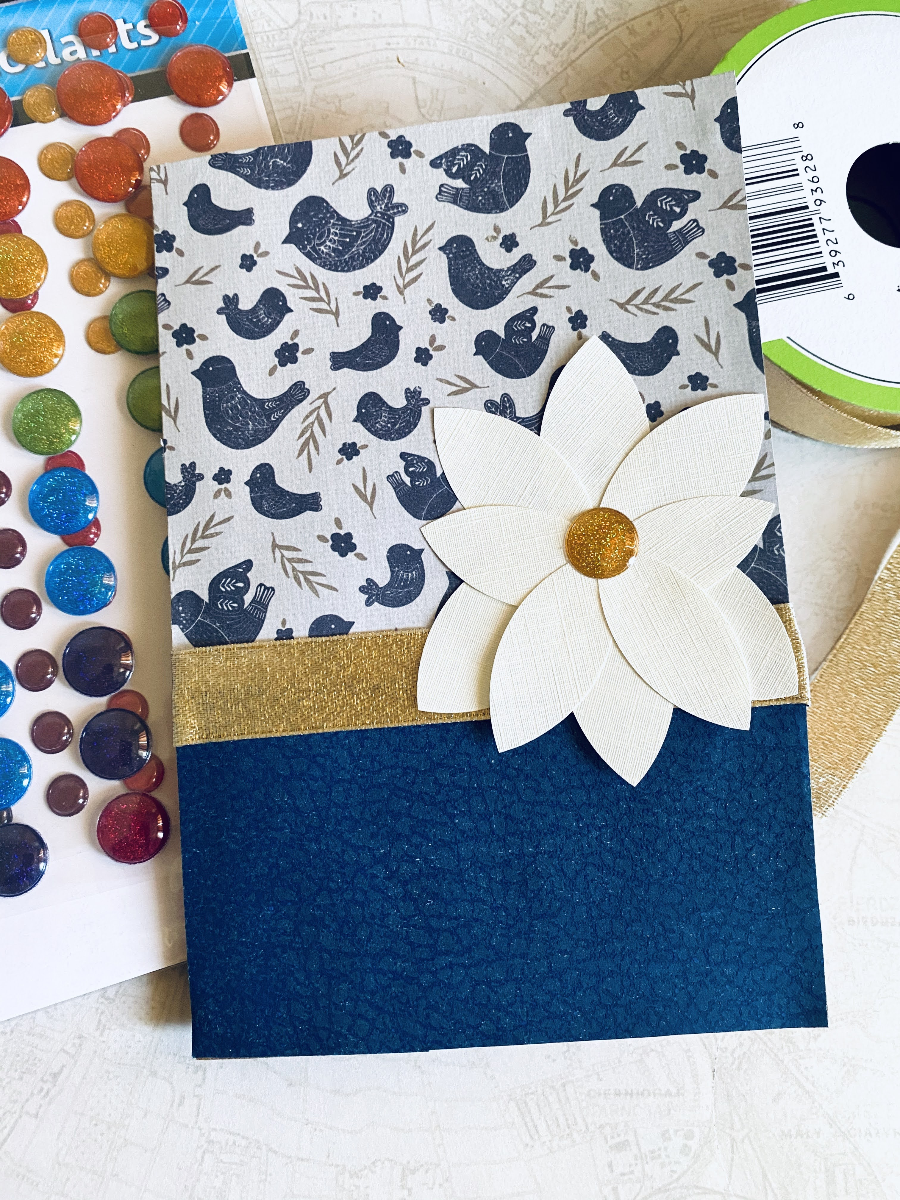 Navy and off-white card with magnolia flower and gold ribbon.  Patterned paper with navy blue birds.