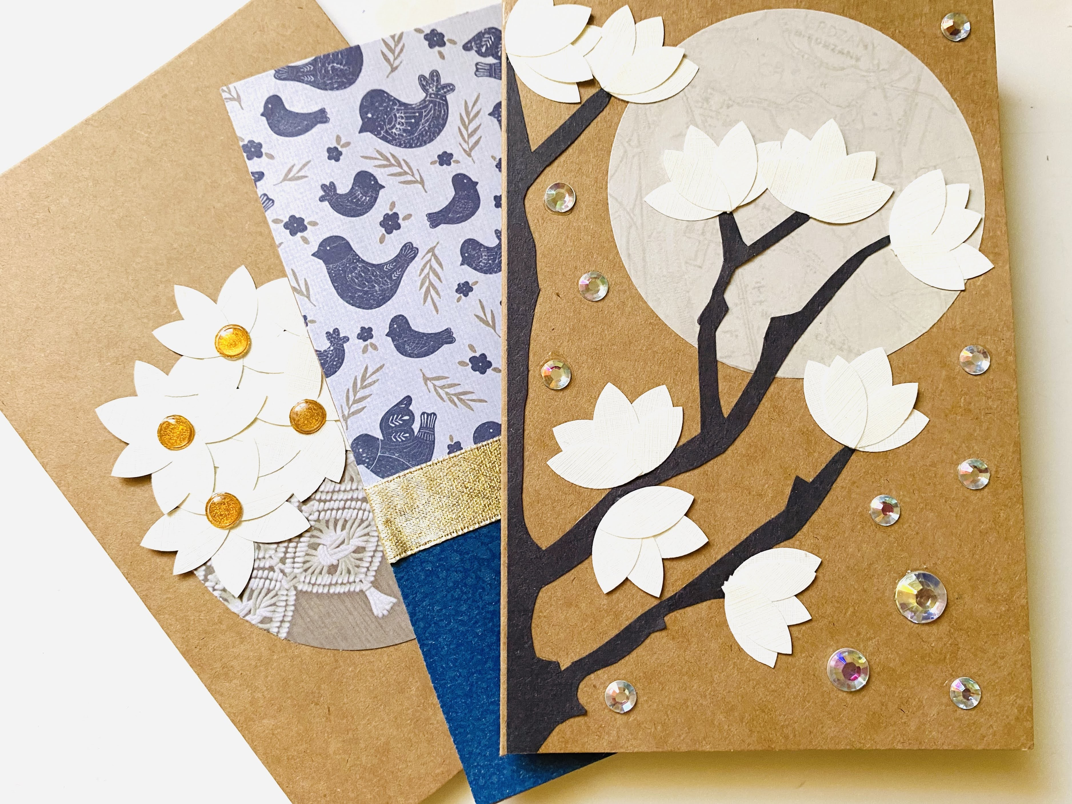 Three homemade cards with magnolias in a basket, against a patterned paper, and a magnolia tree in moonlight.