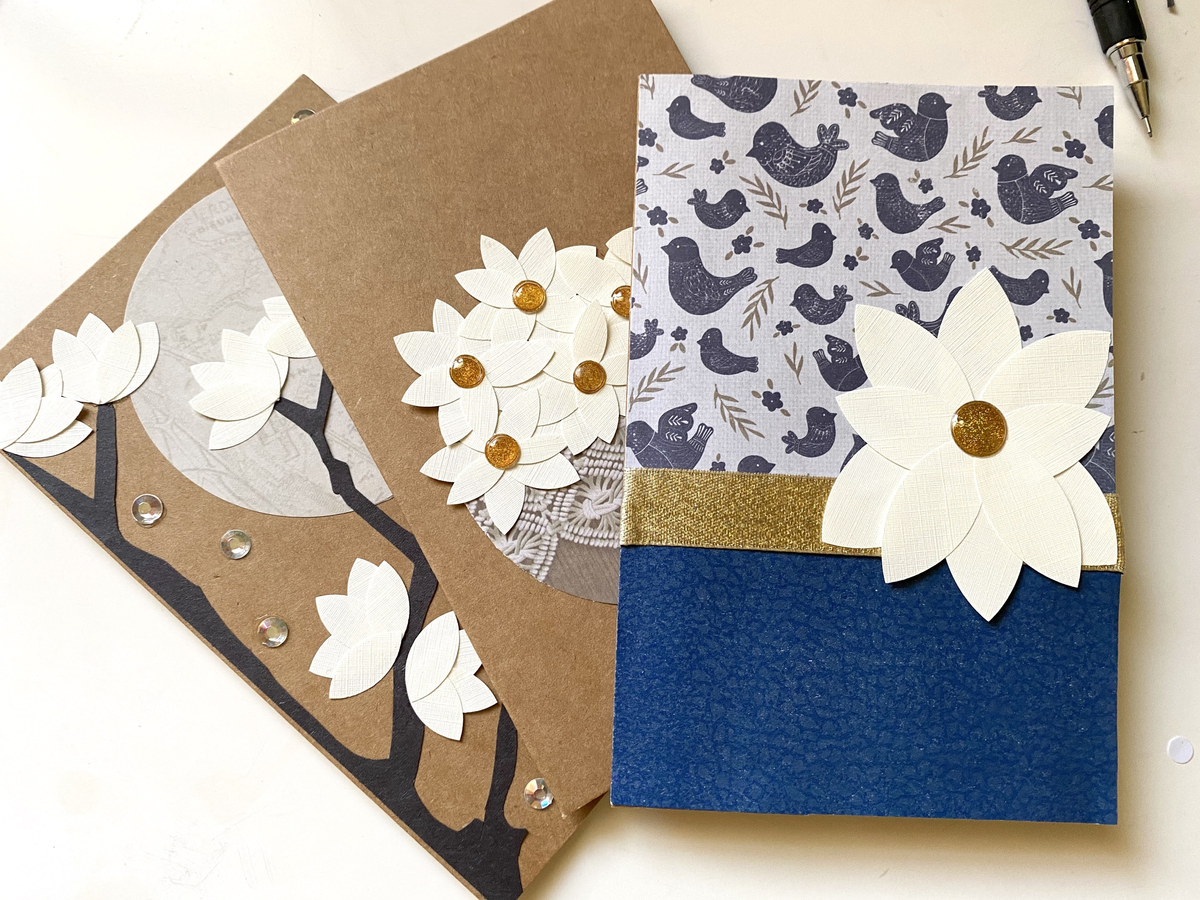 A set of homemade magnolia flower cards made from paper, ribbons, rhinestones, and glittered dots.