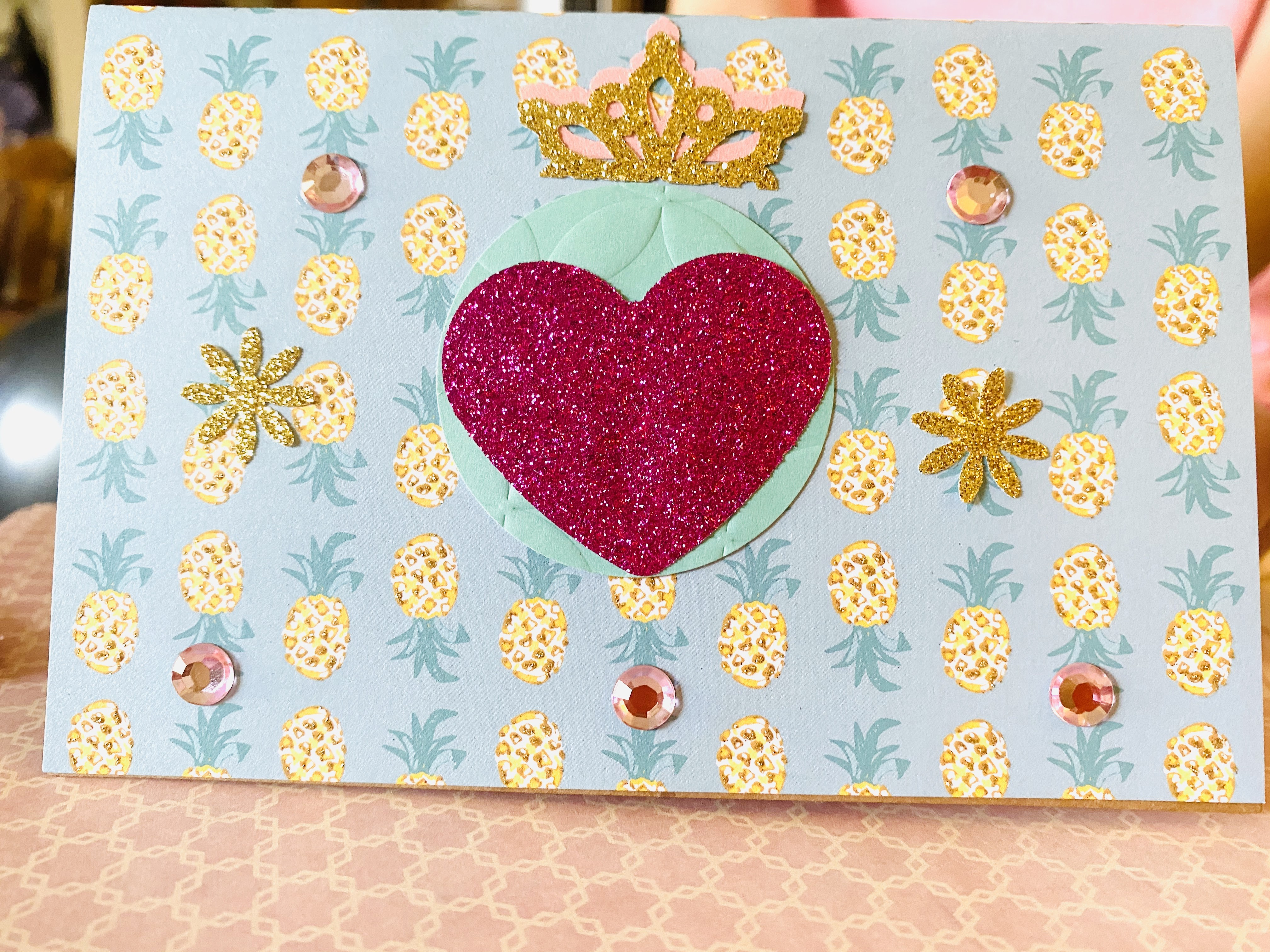 Card with glittered paper, crown, and gemstones.