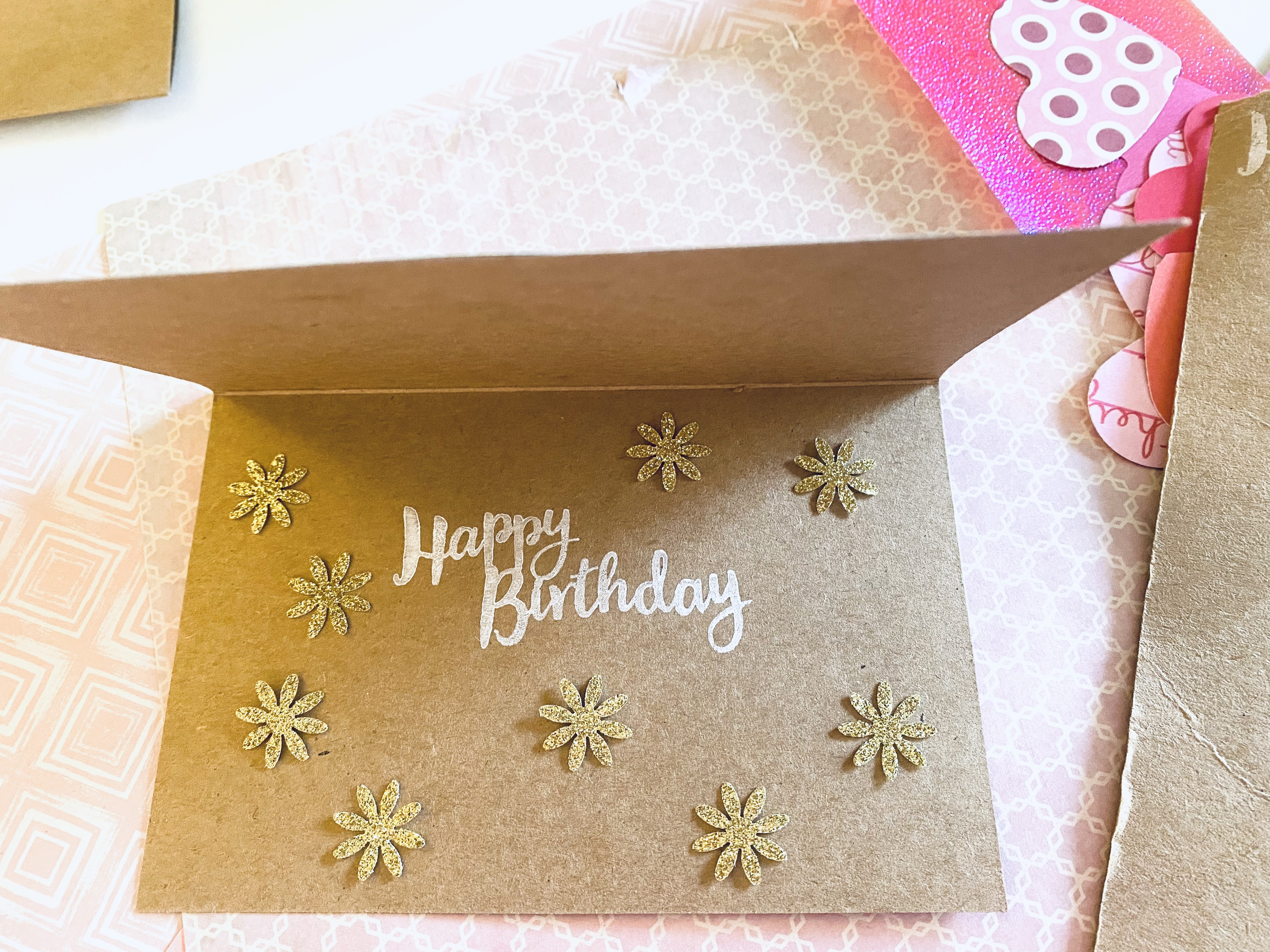 White ink Happy Birthday sentiment. Glittered golden punch out flowers.